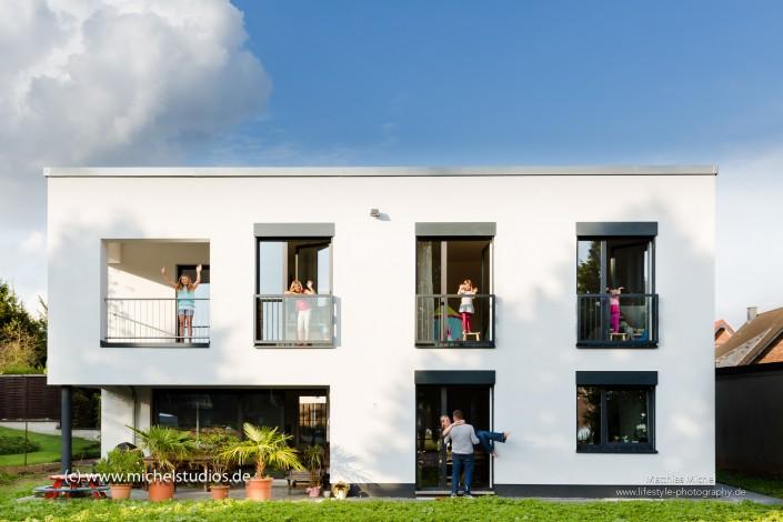 Architekturfoto Familienfoto Neubau mit Familie und vier winkenden Kindern