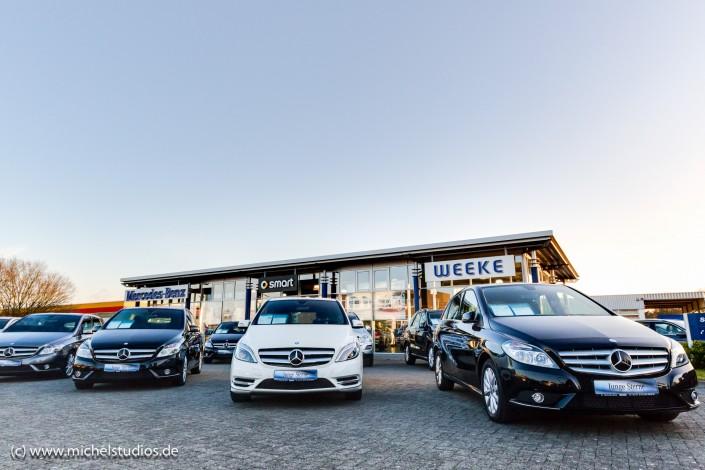 Außenaufnahme eines Autohauses mit mehreren Mercedes Fahrzeugen im Vordergrund